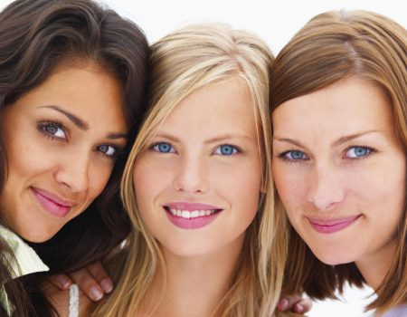 Closeup portrait of smiling young girls isolated on white background